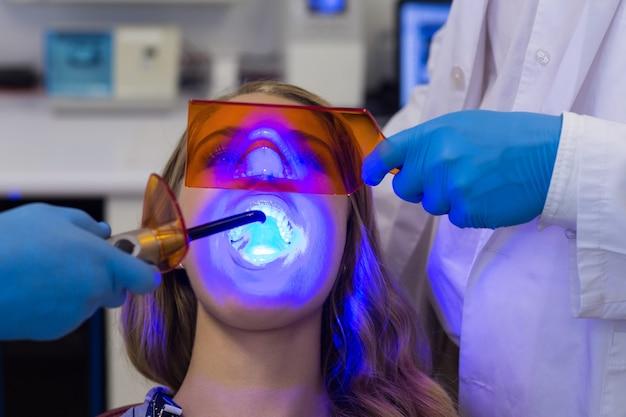 Zahnärzte, die patientin mit zahnheilungslicht untersuchen