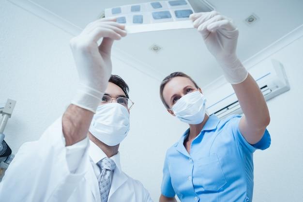 Zahnärzte, die röntgenstrahl betrachten