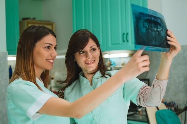 Zahnärzte, die über röntgenstrahl des patienten sich besprechen