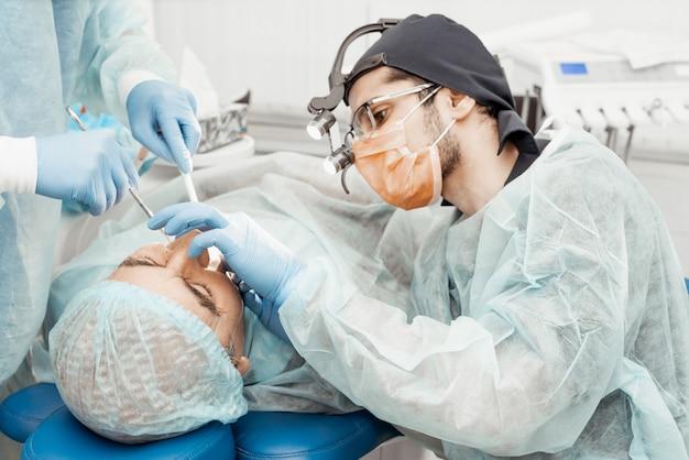 Zahnärzte führen eine operation und implantatinsertion durch. echte bedienung. zahnextraktion, implantate. berufsuniform und ausrüstung eines zahnarztes. gesundheitswesen ausstattung eines arztarbeitsplatzes. zahnheilkunde
