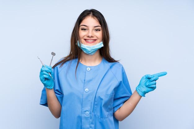 Zahnärztin, die werkzeuge über der blauen wand hält, zeigt finger zur seite