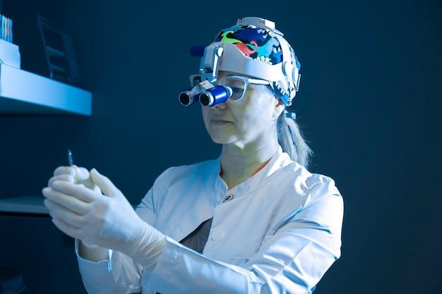 Zahnärztin mit binokularer lupe, die in der zahnklinik arbeitet