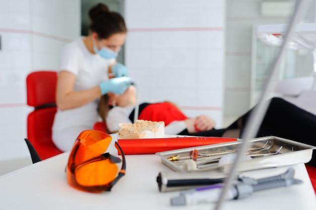 Zahnärztliche instrumente auf dem hintergrund des zahnarztes und des patienten