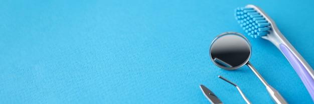 Zahnärztliche instrumente und zahnbürste liegen auf blauem hintergrund. mundpflegekonzept