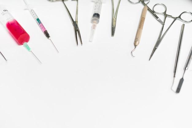 Zahnärztliche werkzeuge, spritzen liegen auf weißem hintergrund