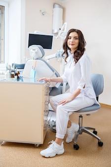 Zahnarzt am arbeitsplatz. fröhlicher arzt sitzt in einem geräumigen modernen büro mit einem freundlichen lächeln