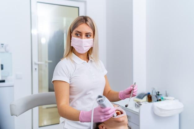 Zahnarzt am arbeitsplatz. zahnaufhellungsprozess. patient im stuhl.