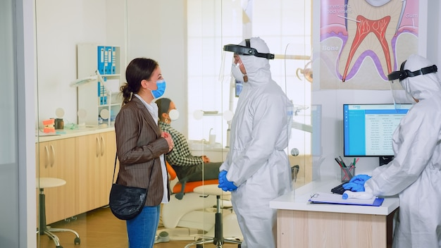 Zahnarzt arzt mit allgemeiner erklärung der zahnbehandlung für patienten im wartebereich, planung von operationsschritten während der globalen pandemie. konzept des neuen normalen zahnarztbesuchs bei ausbruch des coronavirus.