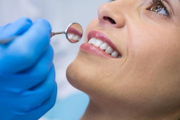Zahnarzt, der abgewinkelten spiegel durch lächelnde frau an klinik hält