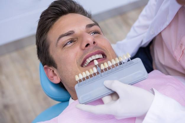 Zahnarzt, der ausrüstung hält, während mann in der medizinischen klinik untersucht wird