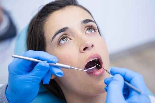 Zahnarzt, der ausrüstungen hält, während frau in der medizinischen klinik untersucht
