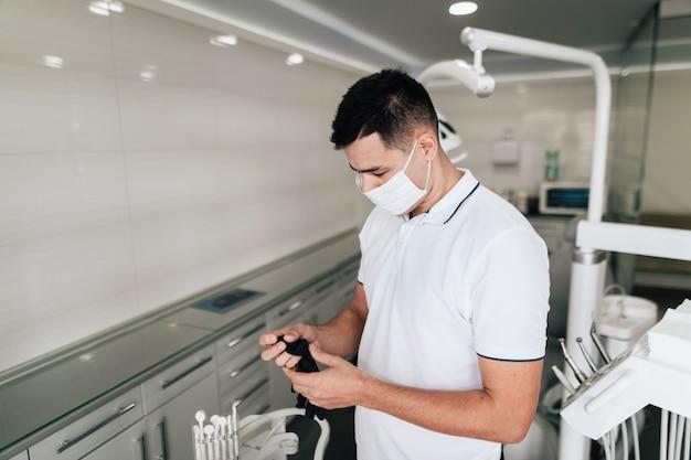 Zahnarzt, der chirurgische handschuhe im büro hält