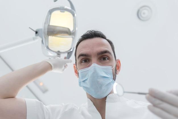 Zahnarzt, der chirurgische maske beim halten des angewinkelten spiegels und des bohrers, bereit zu beginnen trägt