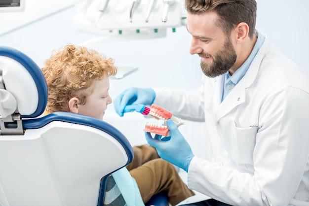 Zahnarzt, der dem jungen zeigt, wie man in der zahnarztpraxis zähne am künstlichen kiefer putzt