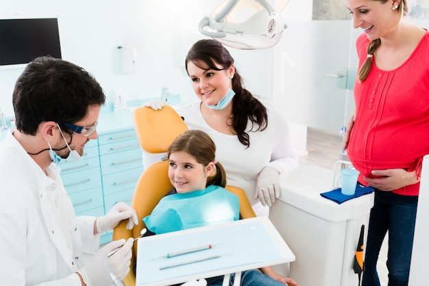Zahnarzt, der dem kind und der mutter zahnmedizinische behandlung gibt