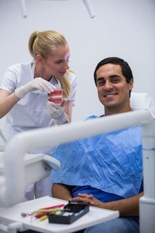 Zahnarzt, der dem patienten einen satz modellzähne zeigt