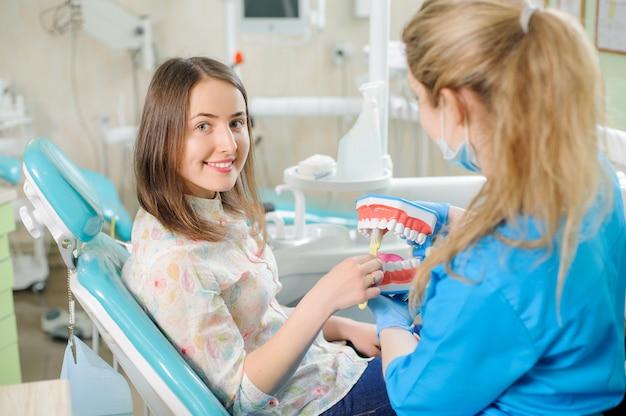 Zahnarzt, der dem patienten in der klinik des zahnarztes zahnmedizinisches kiefermodell zeigt