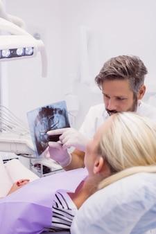 Zahnarzt, der dem patienten röntgen zeigt