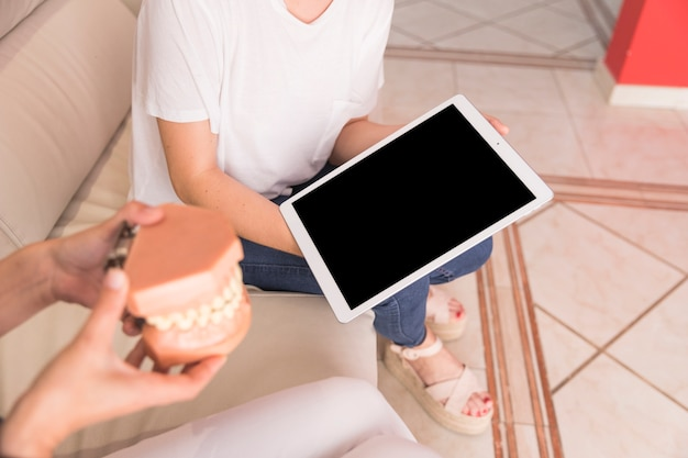 Zahnarzt, der dem patienten zahnmodell zeigt, das digitale tablette hält