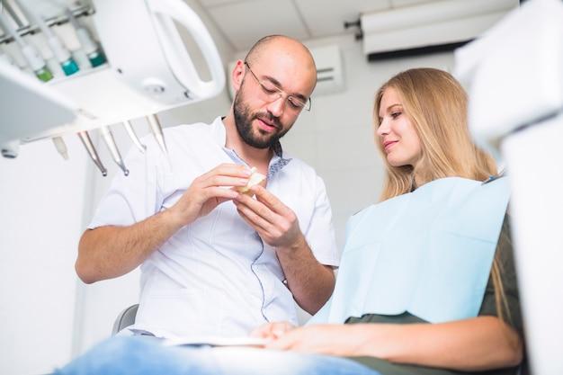 Zahnarzt, der dem weiblichen patienten zahnpflege erklärt