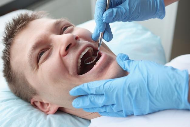 Zahnarzt, der die mundhöhle eines männlichen patienten mit spiegel untersucht. jährliches zahnärztliches kontrollkonzept