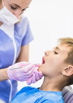 Zahnarzt, der die zähne des jungen mit scaler überprüft