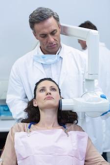 Zahnarzt, der die zähne des patienten röntgt