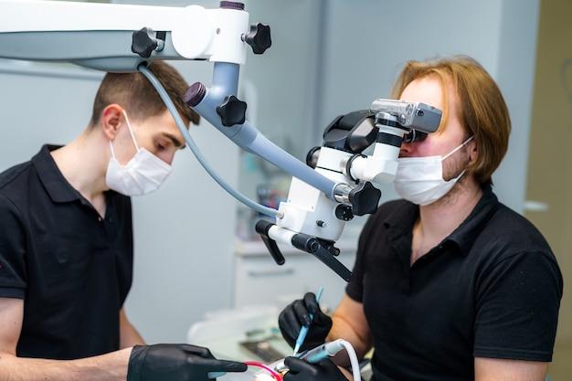 Zahnarzt, der die zähne einer patientin mit einem mikroskop in der stomatologieklinik heilt. behandlungskonzept.