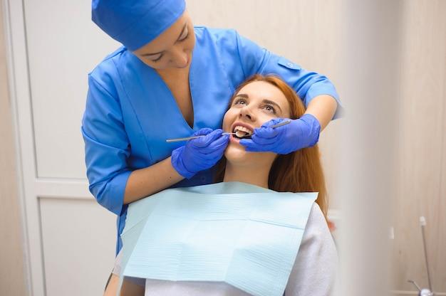 Zahnarzt, der die zähne eines patienten im zahnarzt überprüft.