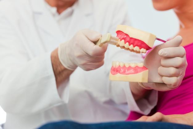 Zahnarzt, der die zähne putzen patienten erklärt