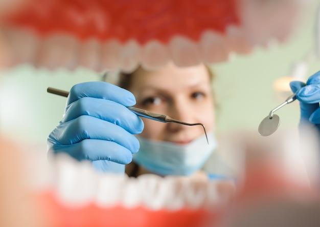 Zahnarzt, der die zahnmedizinische sonde und zahnmedizinischen spiegel hält, die zur zahnprüfung im zahnmedizinischen büro bereit ist.