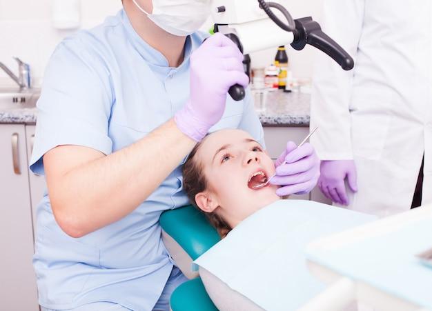 Zahnarzt, der durch die lupe schaut. er benutzt ein mikroskop für die operation in der zahnarztpraxis
