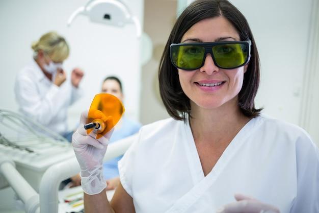Zahnarzt, der ein zahnhärtendes ultraviolettes licht hält