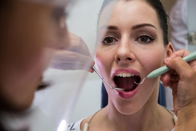 Zahnarzt, der eine patientin mit werkzeugen untersucht
