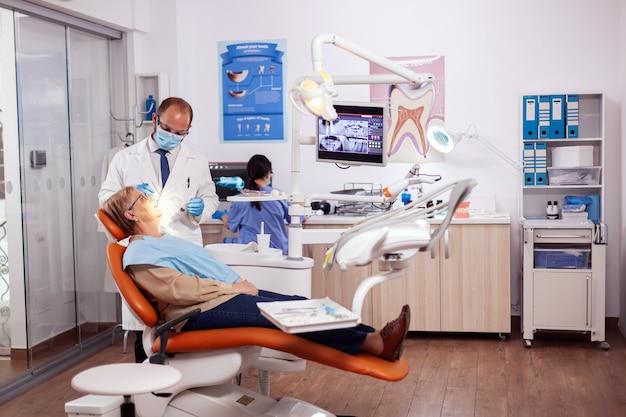 Zahnarzt, der eine zahnärztliche behandlung und intervention durchführt. auf ältere frau. älterer patient während der ärztlichen untersuchung beim zahnarzt in der zahnarztpraxis mit orangefarbener ausrüstung.