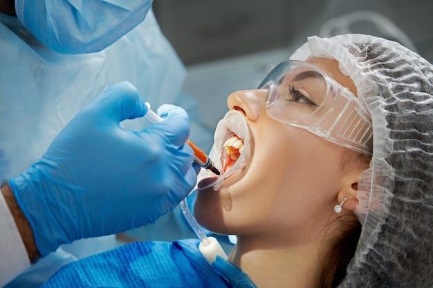 Zahnarzt, der eine zahnbehandlung an einer patientin durchführt. zahnarzt, der die zähne eines patienten in der moderne untersucht