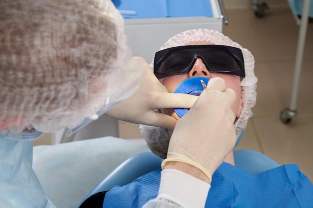 Zahnarzt, der eine zahnbehandlung an einer patientin durchführt. zahnarzt, der die zähne eines patienten in der modernen zahnarztpraxis untersucht