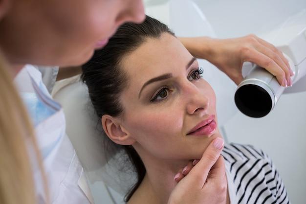 Zahnarzt, der eine zahnröntgenaufnahme einer patientin nimmt