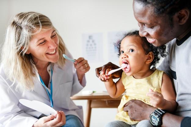Zahnarzt, der einem kleinen mädchen beibringt, wie man ihre zähne putzt