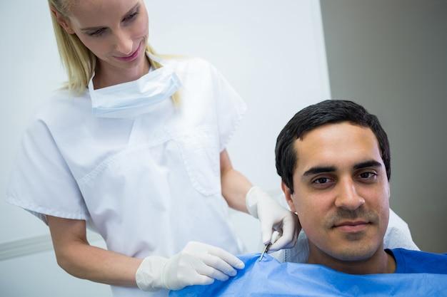 Zahnarzt, der einem patienten hilft, eine zahnschürze zu tragen