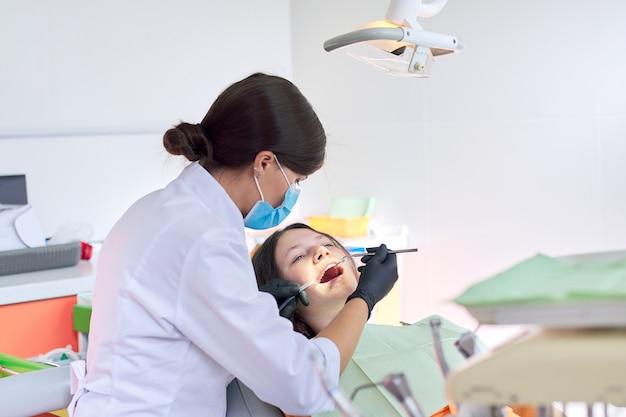 Zahnarzt, der einem patienten in der zahnklinik zähne behandelt