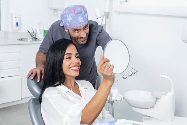 Zahnarzt, der einem patienten in einer klinik das ergebnis einer zahnbehandlung durch einen spiegel zeigt