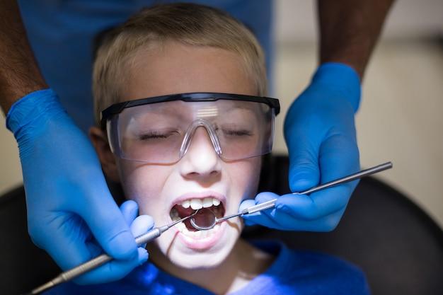 Zahnarzt, der einen jungen patienten mit werkzeugen untersucht