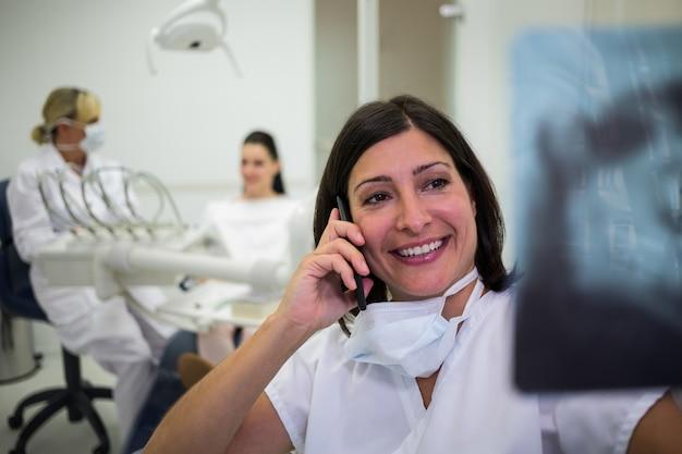 Zahnarzt, der einen röntgenbericht überprüft, während er auf dem mobiltelefon spricht