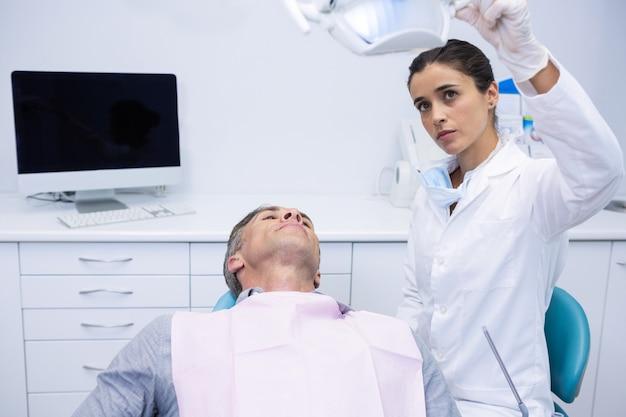 Zahnarzt, der elektrisches licht anpasst, während patient auf zahnarztstuhl sitzt