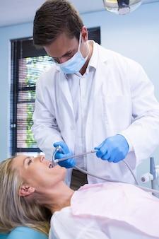 Zahnarzt, der frauenzähne beim stehen gegen wand reinigt