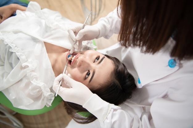 Zahnarzt, der geduldige frauenzähne überprüft