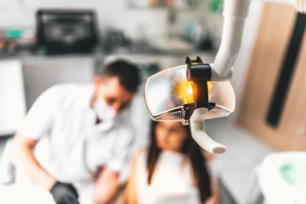 Zahnarzt, der in der zahnmedizinischen klinik mit weiblichem patienten im stuhl arbeitet
