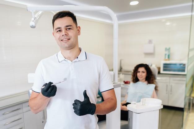 Zahnarzt, der instrument und patienten im büro hält