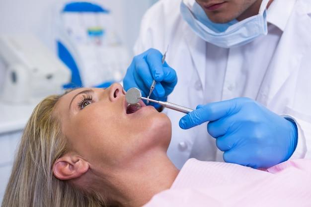 Zahnarzt, der junge frau an der medizinischen klinik untersucht